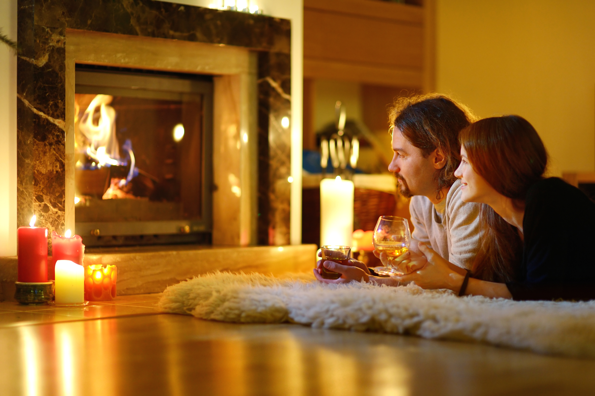 Happy couple having drinks by a fireplace in a cozy dark living room on Christmas eve